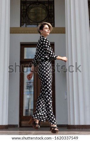 Lifestyle posing lessons in a standing pose. beautiful European model in a black suit with white spots on high heels, pants and a shirt. Long legs, bright makeup, spectacular appearance