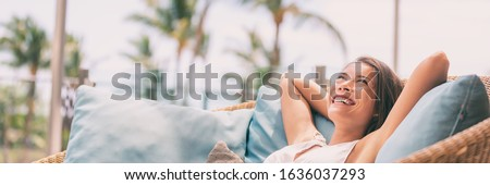 Lifestyle relax happy Asian woman on sofa luxury hotel living banner panoramic. Comfort home summer travel vacation free girl breathing clean air on summer destination panorama. ストックフォト ©