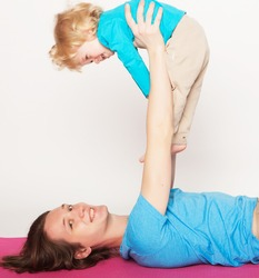 lifestyle, sport  and people concept: father and her son doing yoga exercise on studio white background.