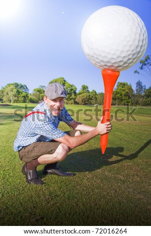 Lifestyle Sports Image Of A Golfer Bending Down On A Golf Course Fairway Holds A Gigantic Golf Ball And Tee In A Funny And Humorous Expression Of Big Golf