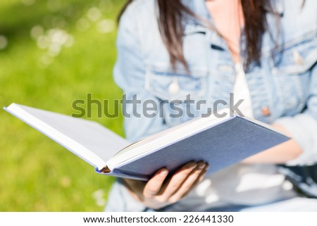 lifestyle, summer vacation, education, literature and people concept - close up of young girl reading book and sitting on grass in park