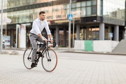 lifestyle, transport and people concept - young man with headphones riding bicycle on city street