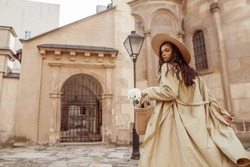 Lifestyle, travel conception: woman wearing straw hat, long trench coat, holding wicker bag with flowers, walking in street of European city. Copy, empty space for text