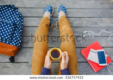 Lifestyle, vacation, education and people concept. Young hipster girl have a tea time outdoor