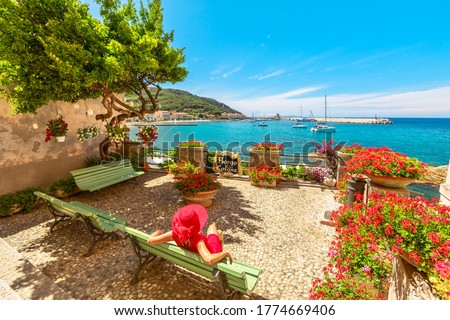 Lifestyle woman in red sitting on bench in Marciana Marina, flowery old district Borgo al Cotone: meaning COTTON VILLAGE, looking harbor bay with ships. Tourist on holiday travel in Italy, Elba island Foto stock ©