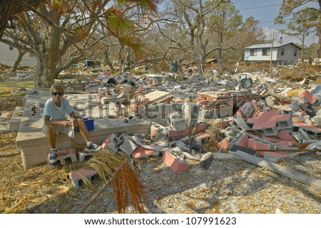 Lifetime woman resident surveying damage and debris in front of her house hit by Hurricane Ivan in Pensacola Florida