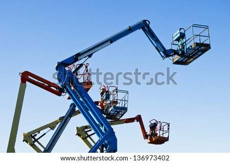 Lift buckets in the air against a clear blue sky