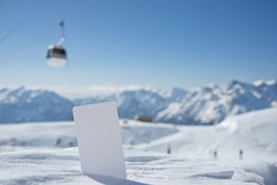 Lift pass card in snow with blurred ski-lift cable car and mountain range. Concept to illustrate winter sport admission fee