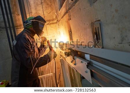 lift worker welding elevator fasteners in lift shaft