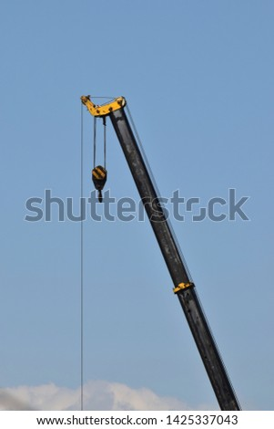 Lifting crane at a construction site of a multistory building against a blue sky in the foothills of the North Caucasus                                #1425337043