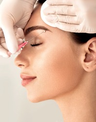 Lifting eyebrow lines using mesothreads. Needle with mesothreads near a female face for contour facial lifting procedure