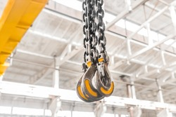 Lifting mechanism iron chain with a hook of an overhead crane on the background of an industrial enterprise or factory