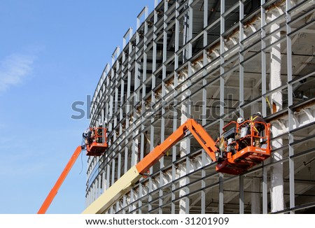 Lifts for workers on metal girders at a new construction site against blue sky