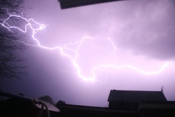 Lighning bolt striking the ground, covering the sky with pure white.