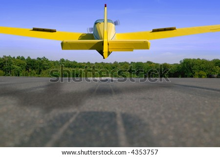 Light aircraft landing on a tarmac runway.