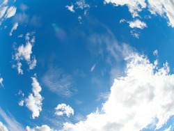 Light, airy sky-scape with white fluffy clouds glowing from bright sunlight and seeming to swirl around the intense blue emptiness.