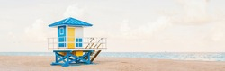 Light airy tropical Florida landscape with blue yellow lifeguard house. American Florida nature ocean view with lifeguard tower, water, sand and sky. Empty beach outdoors. Web banner header.