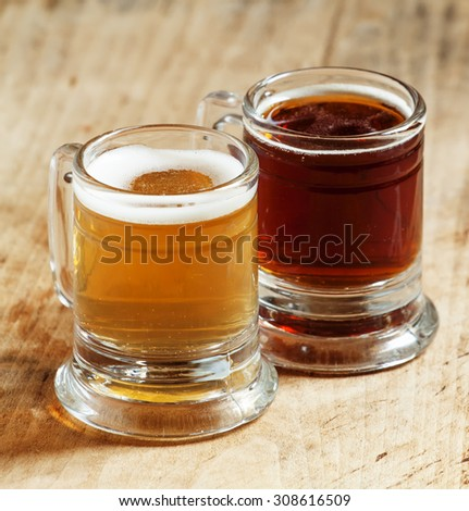 Light and dark beer in old-fashioned circles on old wooden table, selective focus
