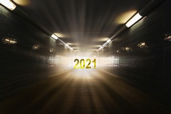 light and 2021 date at the end of the tunnel, symbol for hope for 2021, happy new year 2021 concept