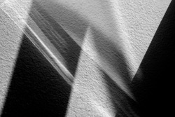 Light and shade lines on the wall. Abstract geometric shapes. Shadow lines on a white wall.