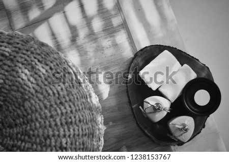 Light and shadow B&W color tone on the granite floor and Warm atmosphere in spa resort, Close up of spa essentials and towels on wooden tray in bathroom, essential oil. Spa products set conception. #1238153767