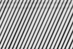 Light and shadow concept, The sunlight shines through the venetian blinds on the concrete wall, Dual toned of black and white in oblique line, Wavy steel stripes design, Abstract background.