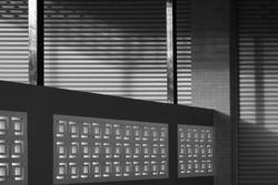 Light and shadow on roller shutter door surface of commercial buildings separated by a concrete fence in black and white style