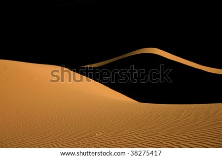 Light and shadow on sand dunes in sahara desert