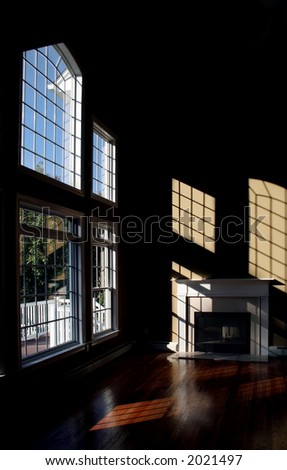 Light and shadows in late afternoon stream across room with fireplace