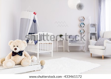 Light and spacious baby room with white furniture, teddy bear in the foreground