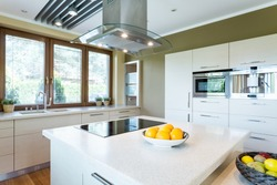 Light and spacious new design kitchen with island and high gloss white furniture