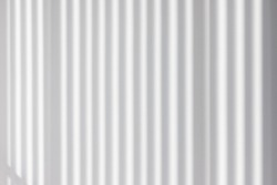 light and striped shadow on white concrete wall. interior design sun protection from wooden batten. house saving energy concept. vertical  abstract shadow pattern background.
