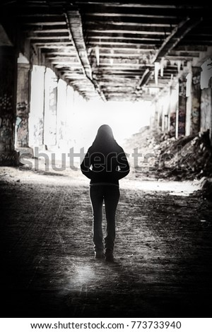 Light at the end of the tunnel.  A  silhouette of a woman walks out of an abandoned subway tunnel walking toward the light. #773733940