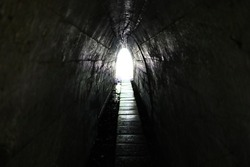 Light at the end of the tunnel. Narrow passage and exit.