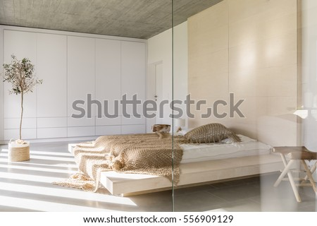Light bedroom with king size bed and white wardrobe