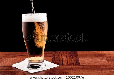 light beer on a bar top isolated on a black background