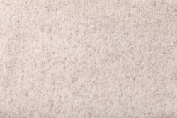 Light beige fluffy background of soft, fleecy cloth. Texture of cream color wool textile backdrop, closeup.