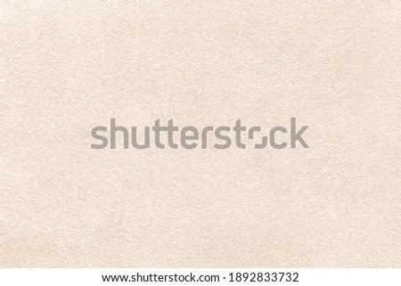 Light beige matte background of suede fabric, closeup. Velvet texture of seamless cream textile, macro. Structure of brown felt canvas backdrop.