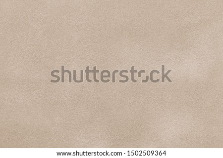 Light beige matte background of suede fabric, closeup. Velvet texture of seamless sand leather.