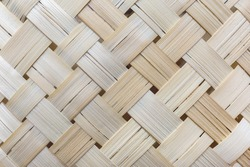 Light beige surface formed by a weave of wood tape, as a background.