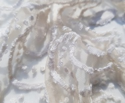 Light beige translucent fabric with a stencil plant print in folds (texture).
