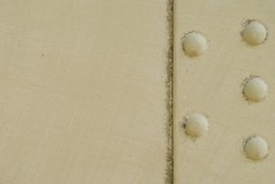 Light beige vintage industrial background texture. An old painted metal surface with a vertical joint line  dividing the image into two parts: еmpty on the left and sidebar with five bolt heads.