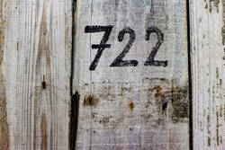 Light beige wooden planks with black number and spider on them