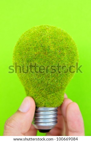 light blub in hand with green background, eco energy concept