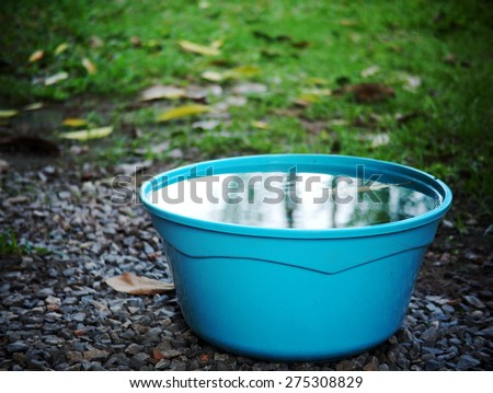 light blue color plastic water bucket on garden floor outdoor surrounding with green area environment and blue sky reflections on the water surface in the bucket