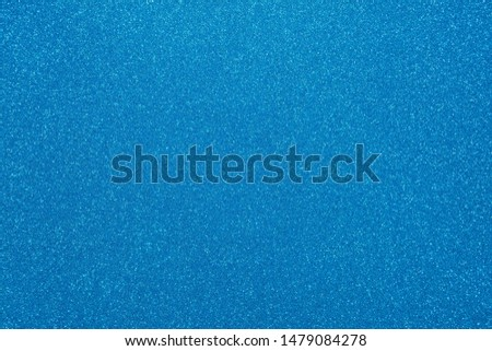 Light blue glitter abstract shiny background. Design paper texture for decoration and design of Christmas, New Year or other holiday pictures. Beautiful packaging material.