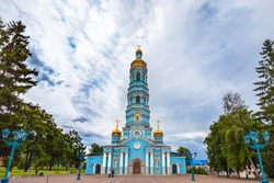 Light blue high church with golden domes surrounded by green trees under large rain clouds on the square. Cathedral of the Nativity of the Virgin, Ufa, Bashkortostan, Russia.
