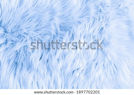 Light blue long fiber soft fur. Blue fur for background or texture. Fuzzy blue fur plaid. Shaggy blanket background. Fluffy fake textile fur. Flat lay, top view, copy space