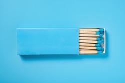 light blue matchbox and light blue match sticks on a light blue background