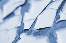 Light blue painted old exterior wall closeup with cracked, scratched and peeling paint, abstract abandoned backdrop, blue flaking paint texture